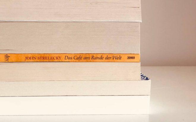 Bücherstapel in der Mitte liegt der gelbe Buchrücken von Cafe am Rande der Welt